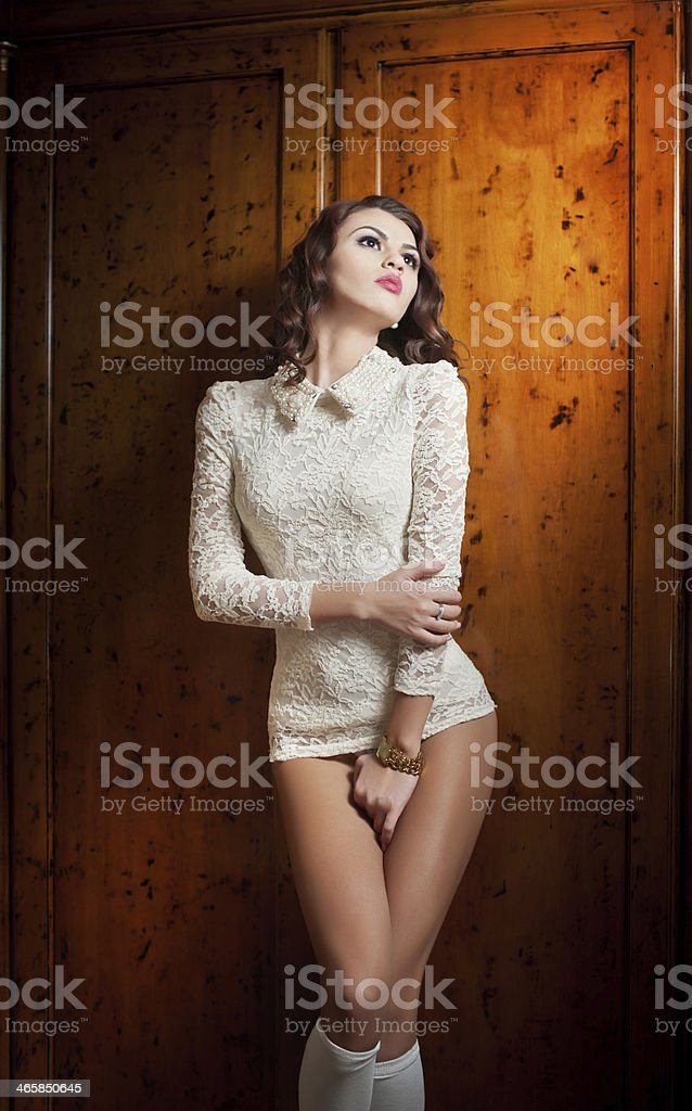 Beautiful brunette woman in white sensual lace outfit posing provocatively stock photo
