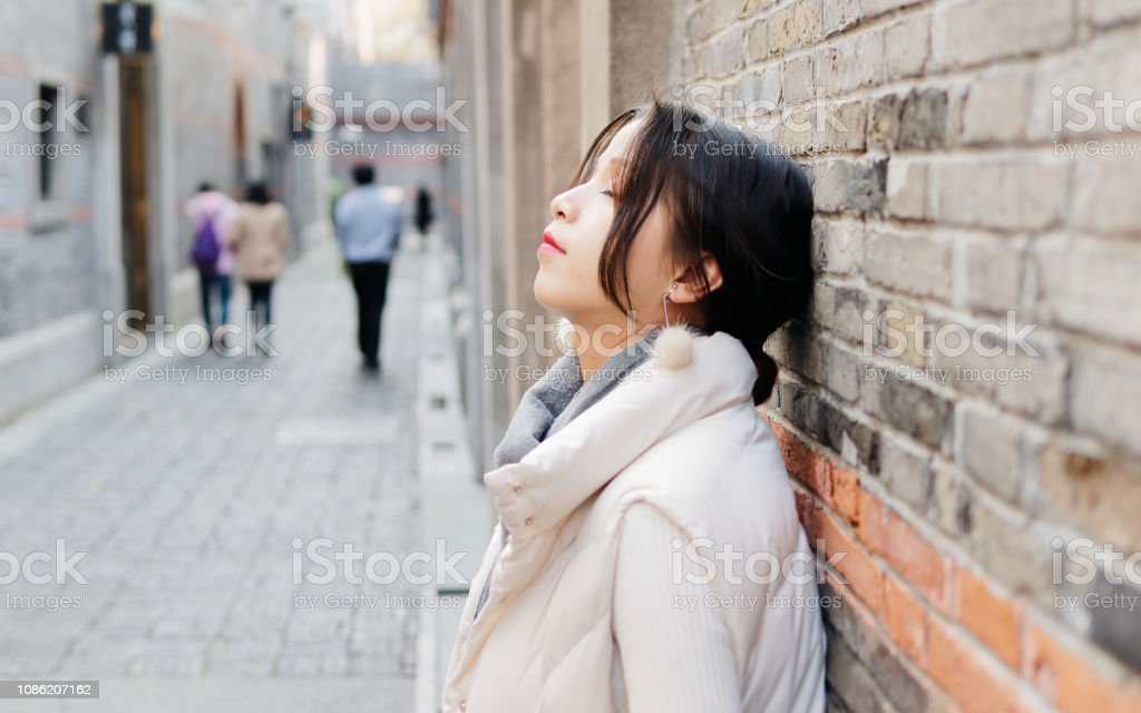 Beautiful Brunette Woman Lean Against Wall With Eyes Closed