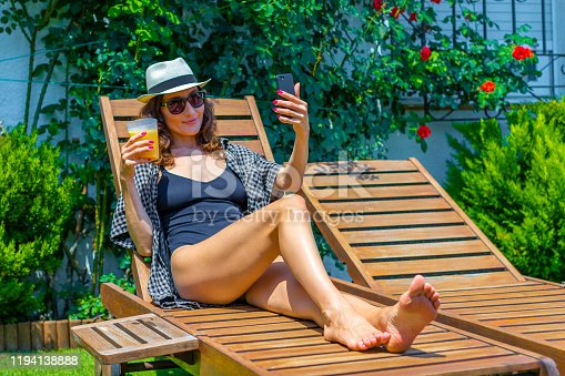 Beautiful brunette woman making selfie with smartphone holding a glass of fresh sangria sitting on sunbed