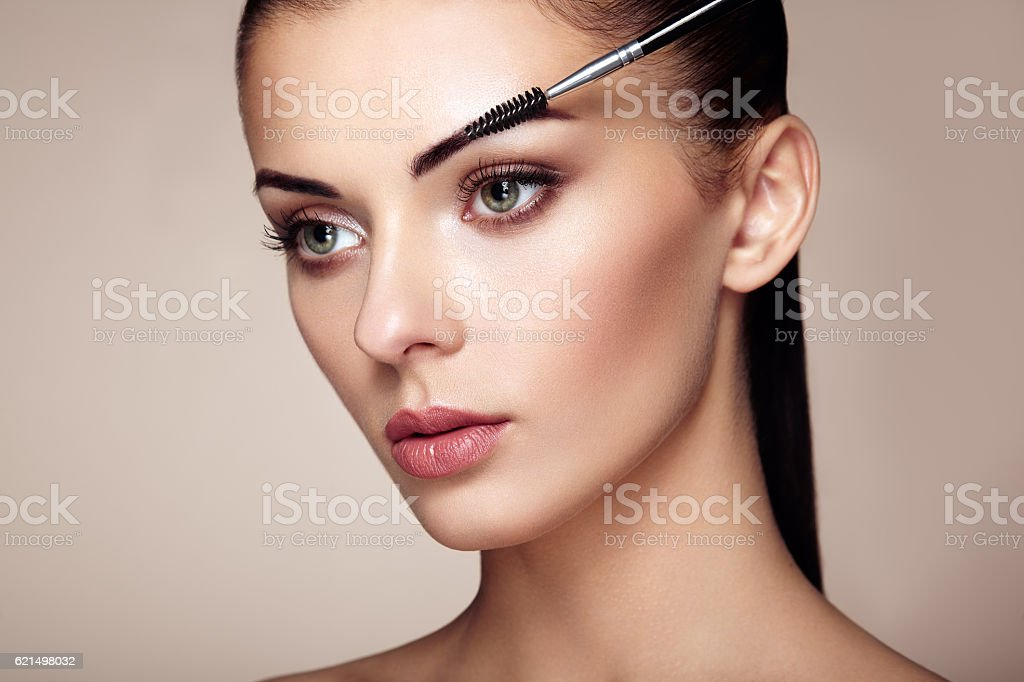 Beautiful brunette woman paints the eyebrows Lizenzfreies stock-foto