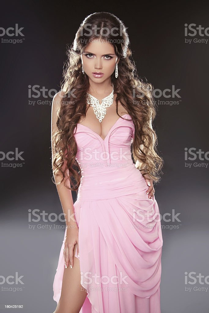 Beautiful brunette woman posing in pink gorgeous dress isolated royalty-free stock photo