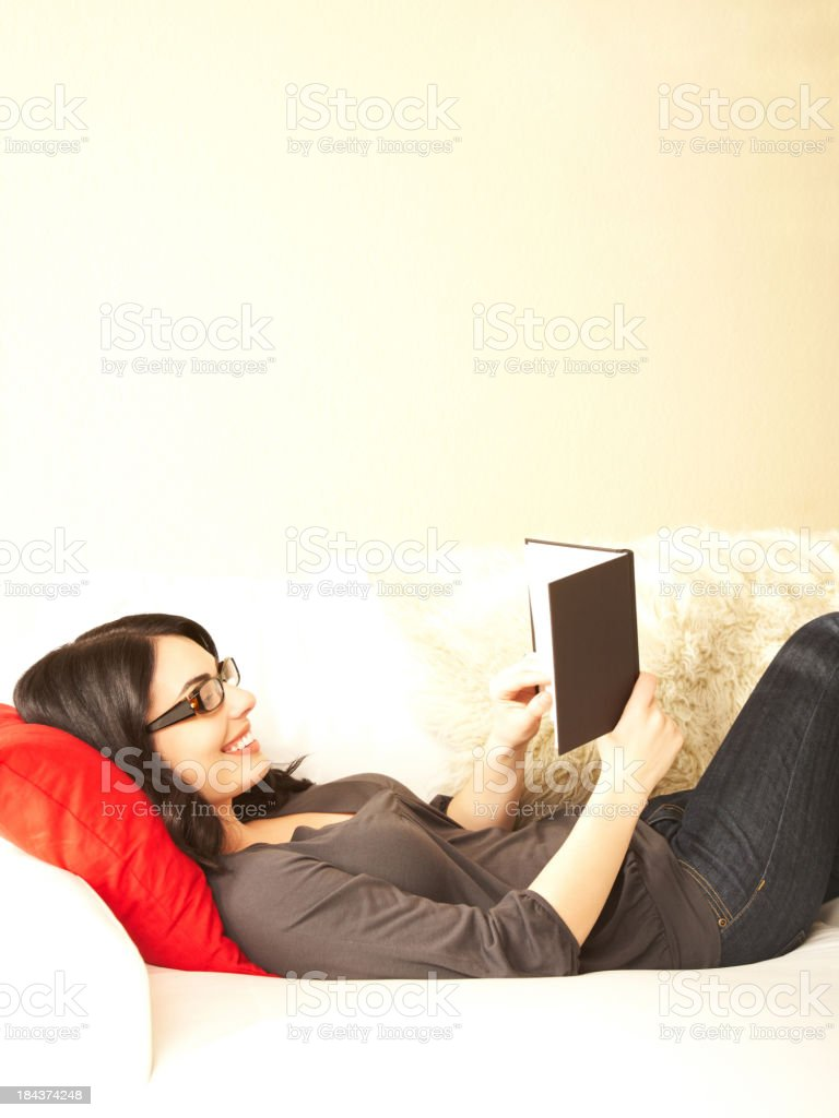 Beautiful brunette woman relaxing while reading a book on sofa royalty-free stock photo