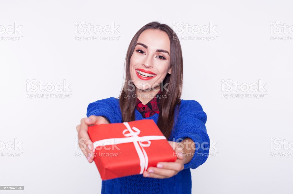 Beautiful brunette woman smiling with gift box in hands on the white background. royalty-free stock photo
