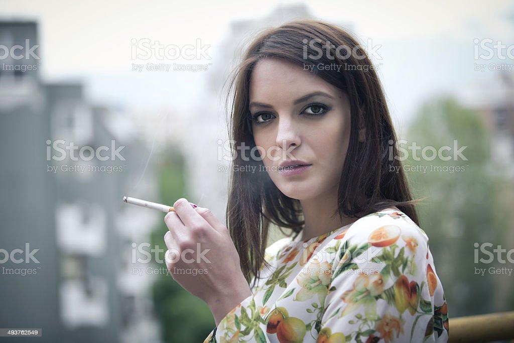 Beautiful brunette woman smoking addict smoking a cigarette stock photo