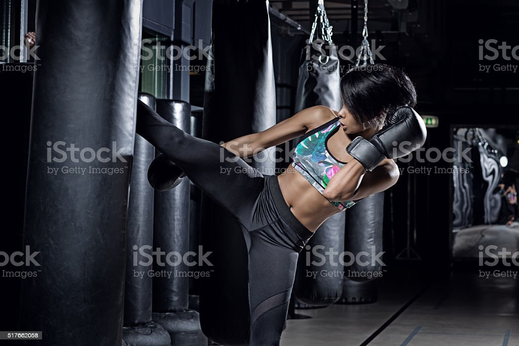 Beautiful brunette woman training during kickboxing workout at gym stock photo