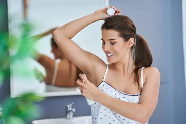 Schöne brünette Frau mit Deodorant im Badezimmer – Foto