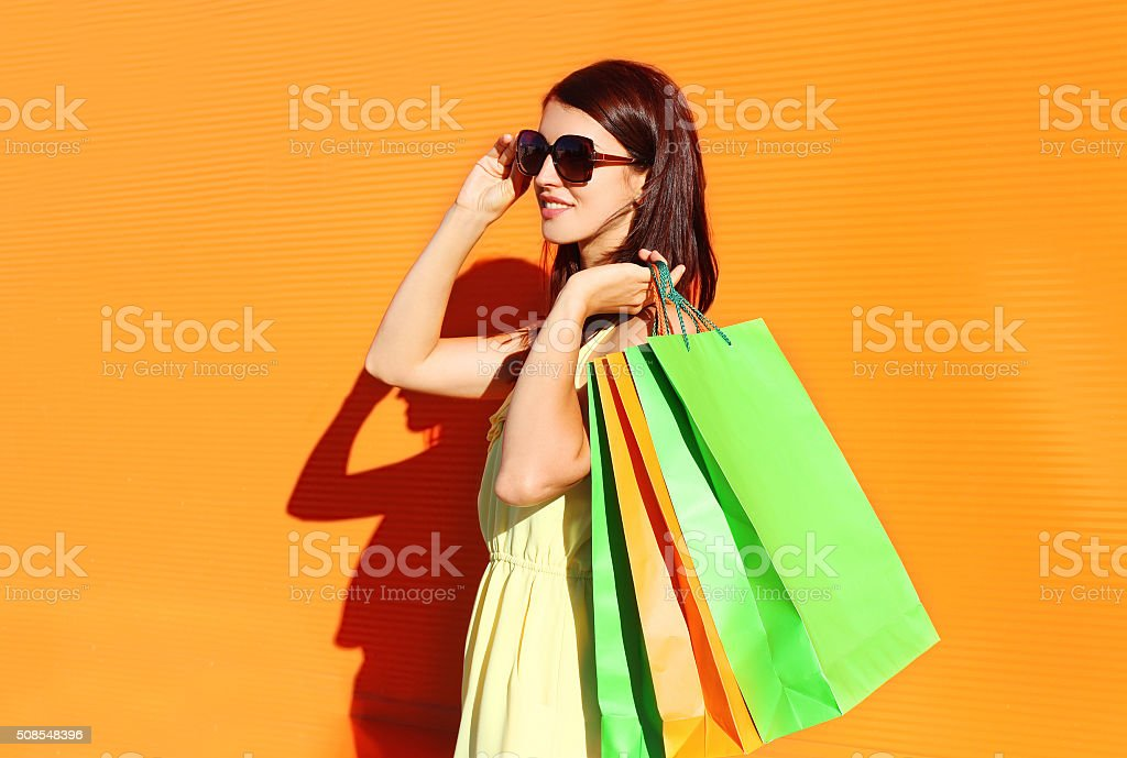 Beautiful brunette woman wearing a dress with shopping bags in city
