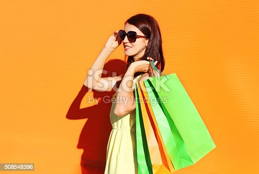 istock Beautiful brunette woman wearing a dress with shopping bags 508548396