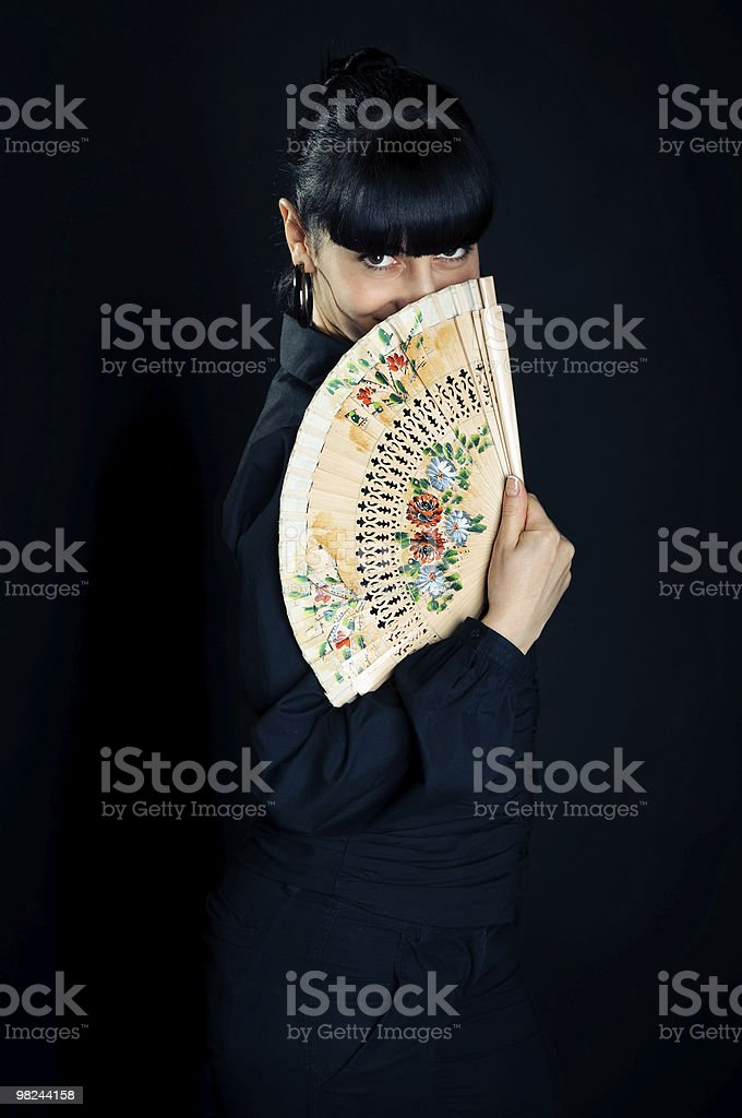 beautiful brunette woman with a fan on black background royalty-free stock photo