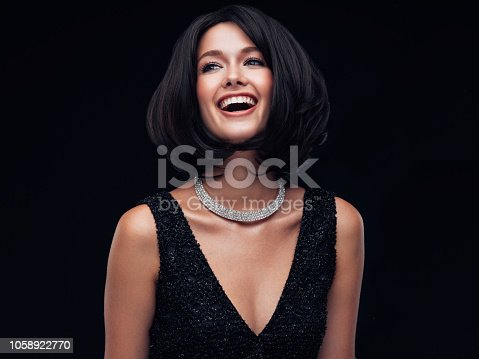 Beautiful brunette woman with beautiful hairstyle and make-up wearing jewelry