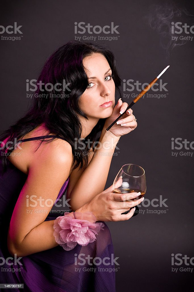 Beautiful brunette woman with cigarette and glass of whisky royalty-free stock photo