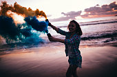 Beautiful brunette woman with colorful smoke bombs at a beach