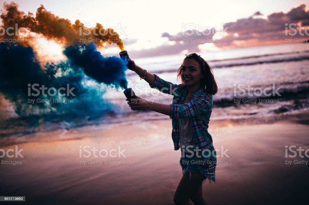 Hermosa mujer morena con bombas de humo coloridas en una playa - foto de stock
