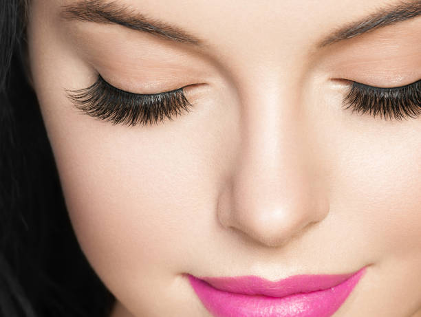 Beautiful brunette woman with eyelashes extension and long brunette curly hairstyle pink lipstick. Beautiful brunette woman with eyelashes extension and long brunette curly hairstyle pink lipstick. Studio shot. false eyelash stock pictures, royalty-free photos & images