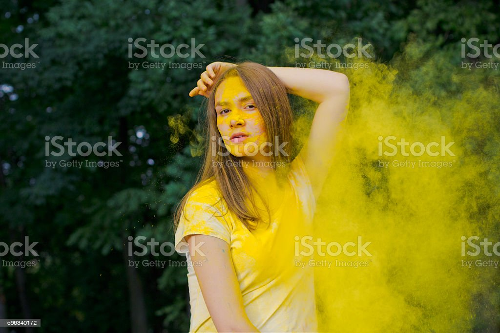 Beautiful brunette woman with yellow paint Holi royalty-free stock photo
