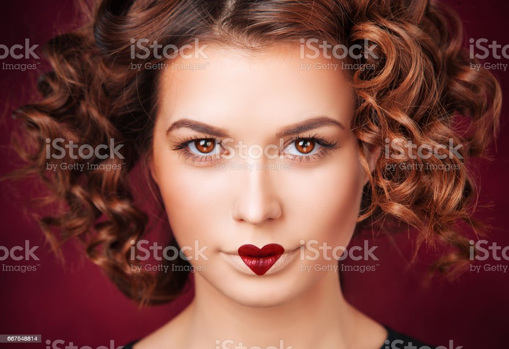 Beautiful Brunette Woman Young Girl With Curly Hair On Valentines Day With Heart Shaped Sign Paint On Lips Creative Makeup Isolated On Deep Red Background Wall Closeup Portrait Love Concept Stock Photo