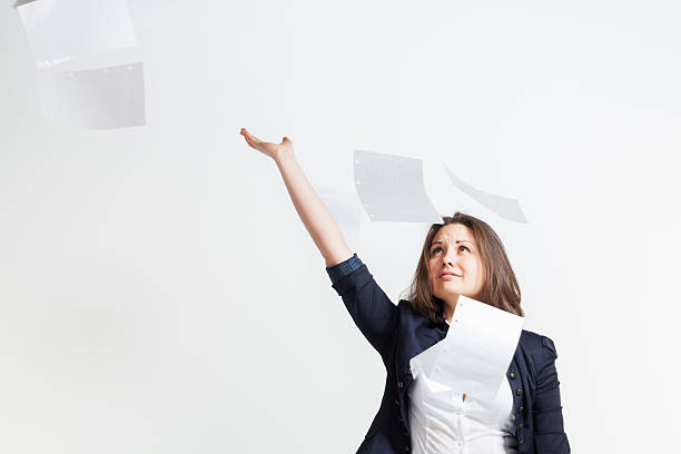 Beautiful brunette young business woman throwing papers stock photo