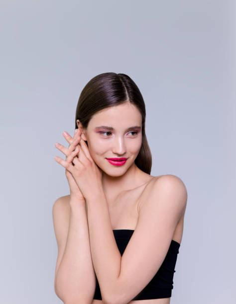 schöne brünette junge frau mit glühendem make-up auf grauem hintergrund fashion-modell aus nächster nähe erschossen - schmale schulter stock-fotos und bilder