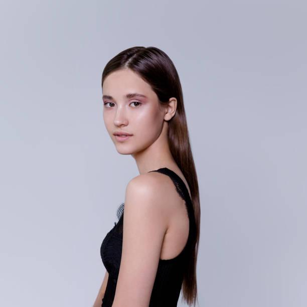 schöne brünette junge frau mit natürlichem farb-make-up auf grauem hintergrund fashion-modell taillenaufnahme erschossen - spitzen crop tops stock-fotos und bilder