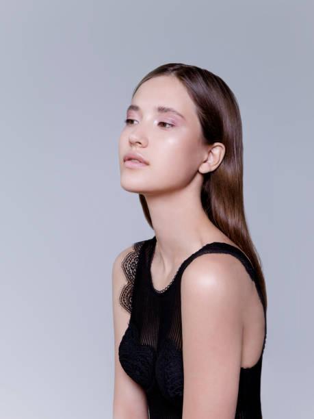 schöne brünette junge frau mit natürlichem farb-make-up auf grauem hintergrund fashion-modell taillenaufnahme erschossen - schmale schulter stock-fotos und bilder