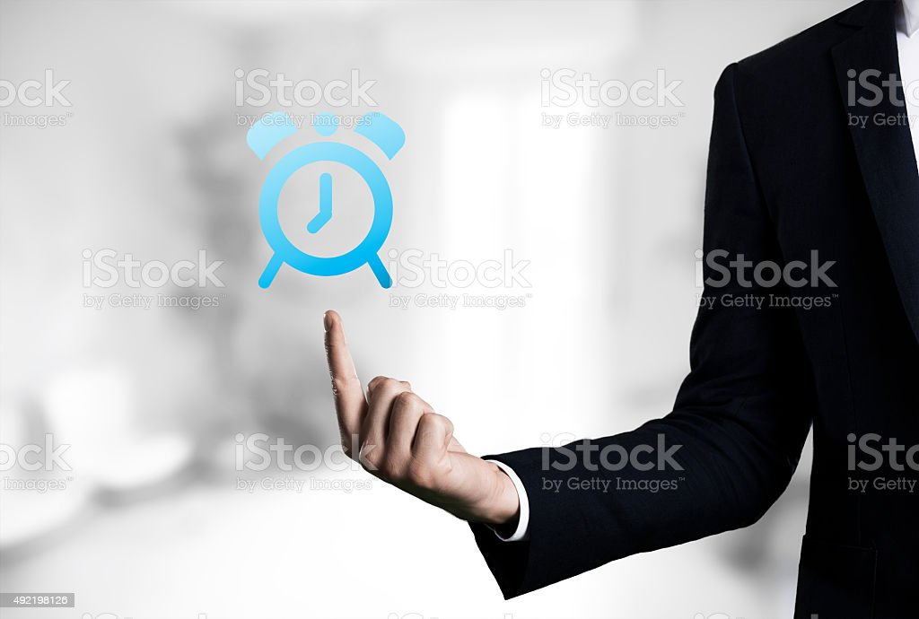 beautiful Business male arm indicating alarm clock icon stock photo