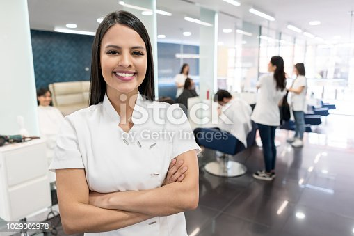 Beautiful business owner of a hair salon looking at camera very happy smiling with arms crossed and customers at the background geeting a haircut