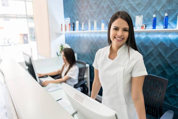 schöne eigentümer von einem haar salon stehen hinter der rezeption lächelnd in die kamera - schönheitssalon stock-fotos und bilder