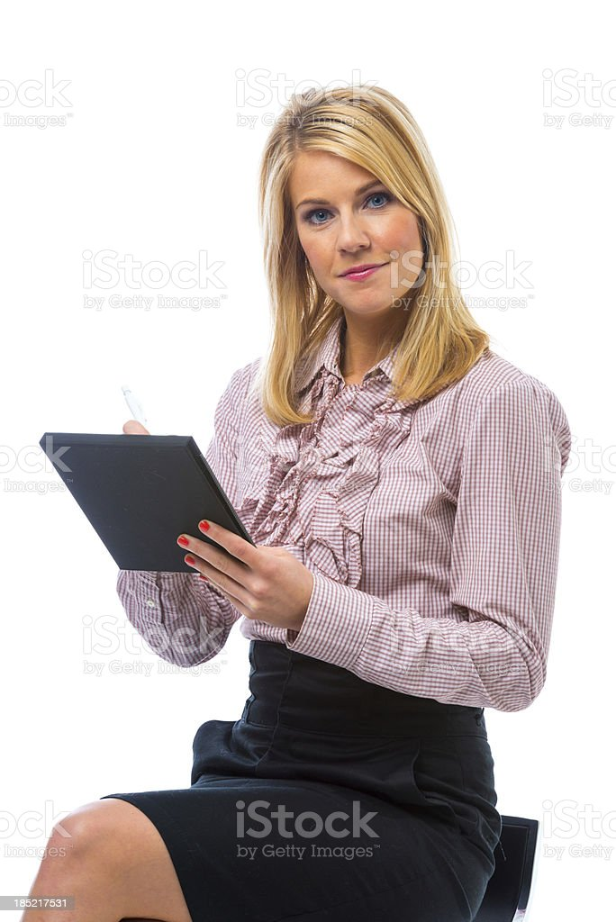 Beautiful business secretary sitting on chair and taking notes stock photo