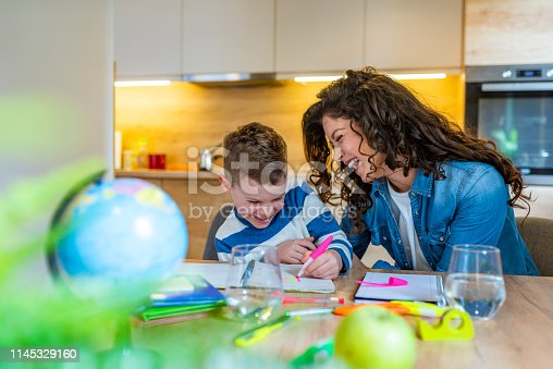 1020504438istockphoto Beautiful business woman and her cute little son are drawing and smiling while sitting in kitchen 1145329160