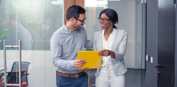 Beautiful business woman and man walking through office hall and discussing business documents stock photo