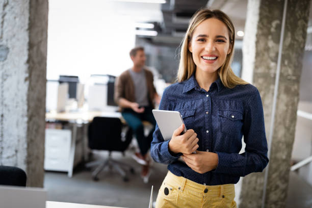 Beautiful business woman holding tablet computer in office stock photo
