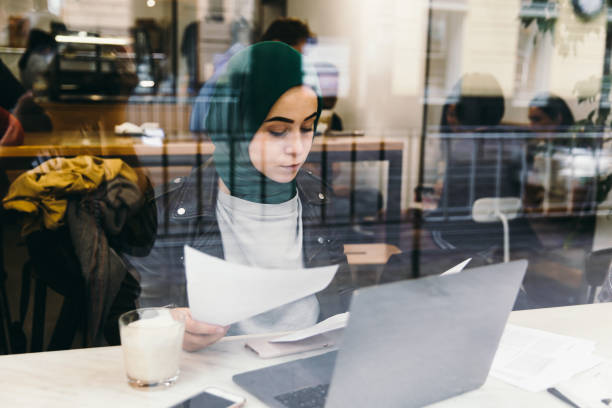 Beautiful business woman in hijab working with laptop in cafe stock photo