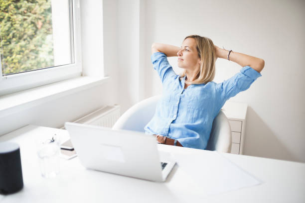 beautiful business woman is relaxing in her homeoffice stock photo