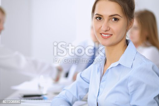istock Beautiful business woman on the background of business people 827208890