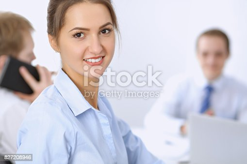 istock Beautiful business woman on the background of business people 827208946