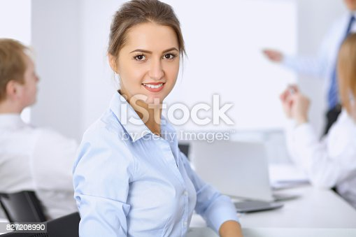 istock Beautiful business woman on the background of business people 827208990
