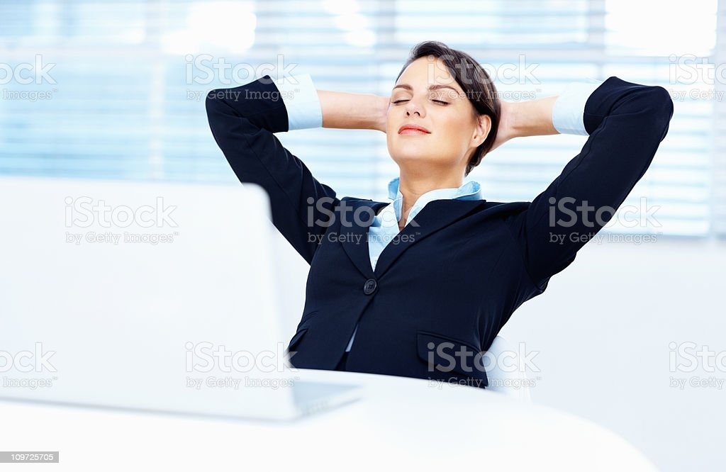 Beautiful business woman relaxing with eyes closed in office royalty-free stock photo