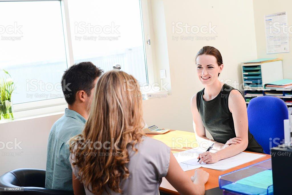 Belle femme d'affaires à la vente de transaction avec jeune couple dans le bureau - Photo