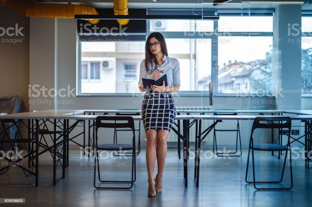 Femme daffaires belle assis sur le bureau et la tenue pour