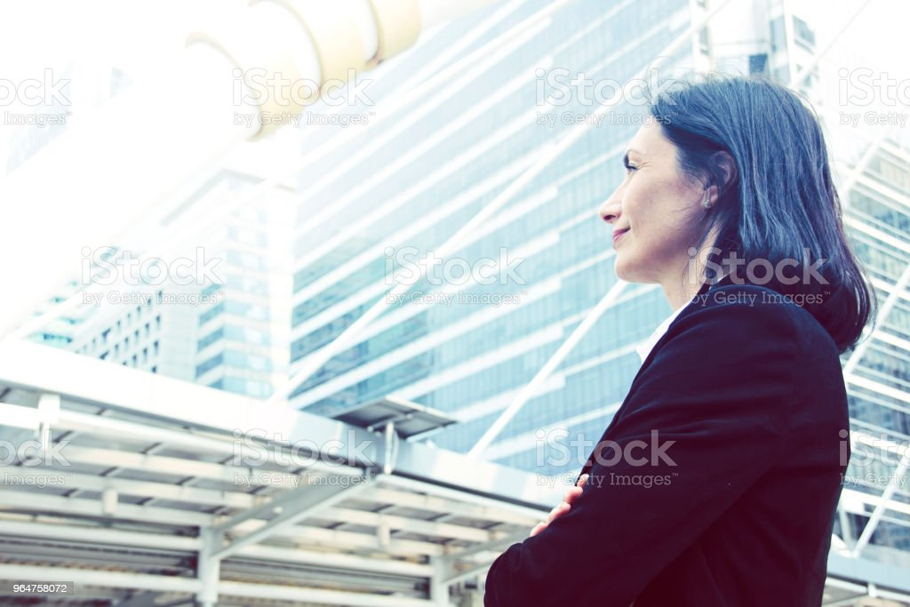 Beautiful business woman smiling and looking offices building background, blue color shape. royalty-free stock photo