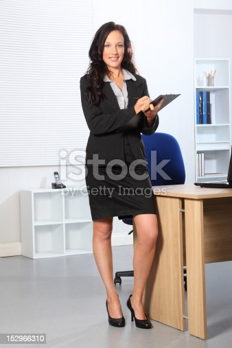 471445335istockphoto Beautiful business woman standing with clipboard 152966310
