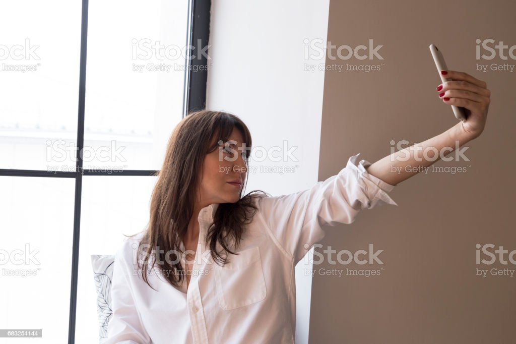 Beautiful business woman taking a selfie by the window 免版稅 stock photo