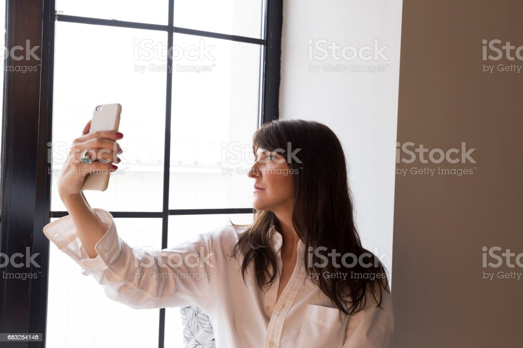 Beautiful business woman taking a selfie by the window royalty-free stock photo