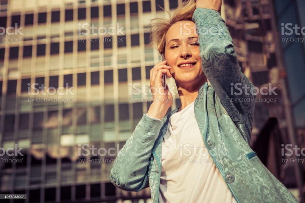 Beautiful business woman talking on a cell phone in front of the office building stock photo