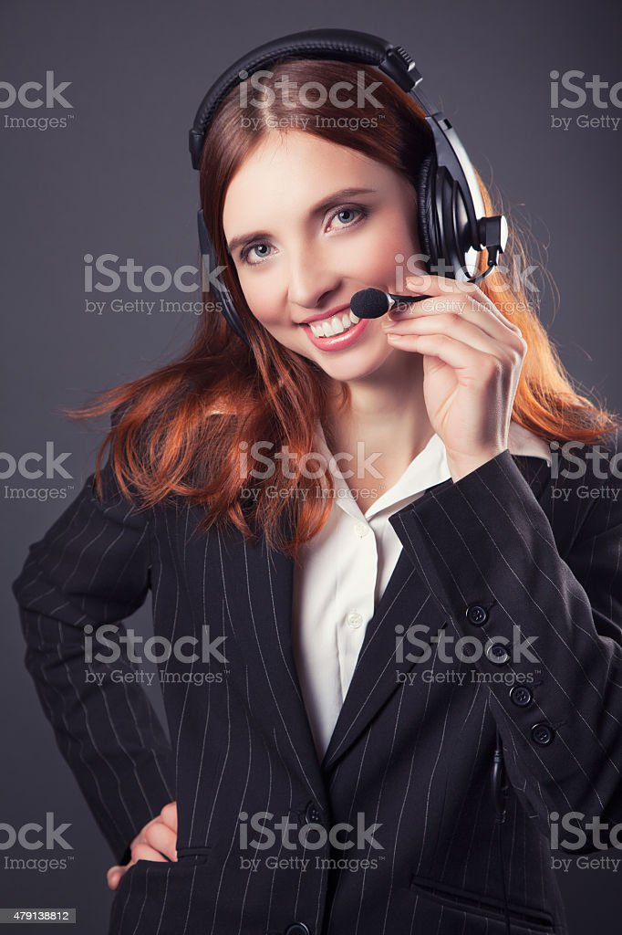 beautiful business woman with headphones against dark grey backg stock photo