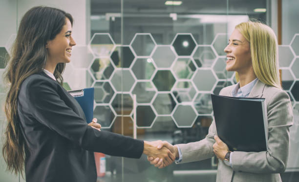 Beautiful business women shaking hands in office stock photo
