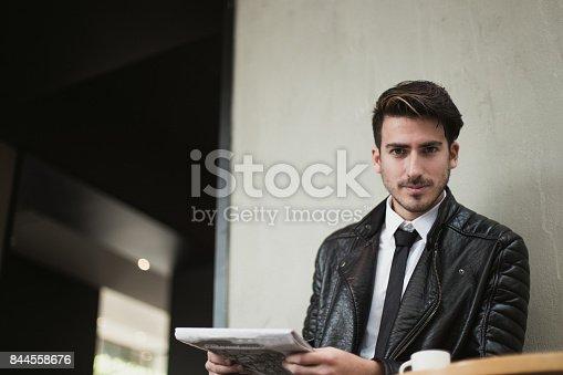 istock Beautiful businessman reading the news 844558676
