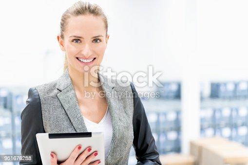 915900234istockphoto Beautiful businesswoman at warehouse 951676288