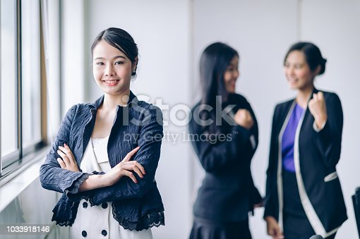 istock Beautiful Businesswoman cross one's arm and smiling to success job while business partner in background have a brainstorm 1033918146