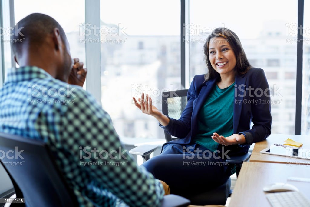 Beautiful businesswoman discussing with male colleague in creative office. Young executives are sitting on chairs against window. They are wearing smart casuals. stock photo